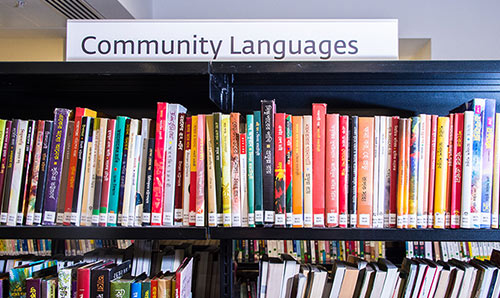 Row of community languages books in a library