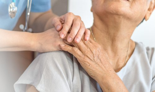 Close up of an older woman in healthcare setting, with healthcare worker's hand on her shoulder
