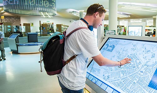 young man exploring a digital map in Manchester Centre Library